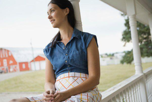 Thoughtful woman sitting on porch