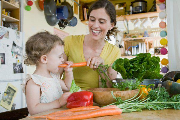 mother and daughter in the kitchen with vegetables
